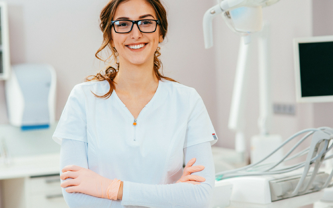 Confident associate dentist smiling with arms crossed