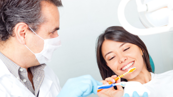 Mask-wearing dentist offering two toothbrushes to patient