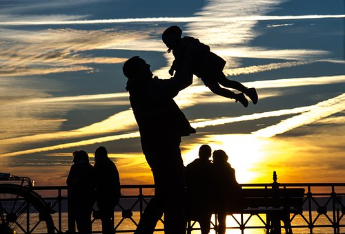 Father lifts young daughter above his head in shadows at sunset