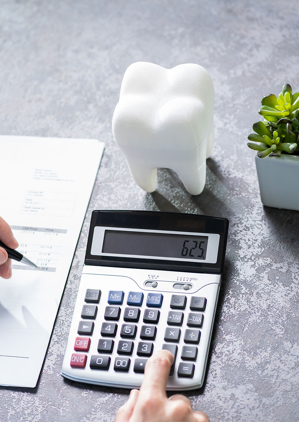 Dental accountant using calculator beside large model tooth