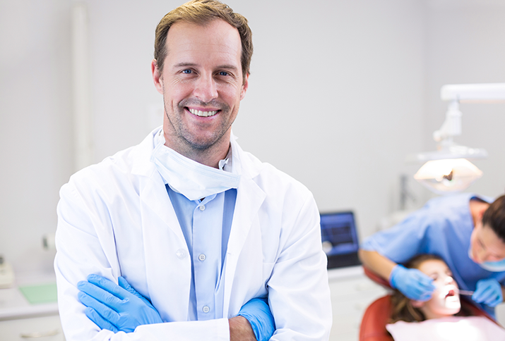Smiling dentist in lab coat crossing arms