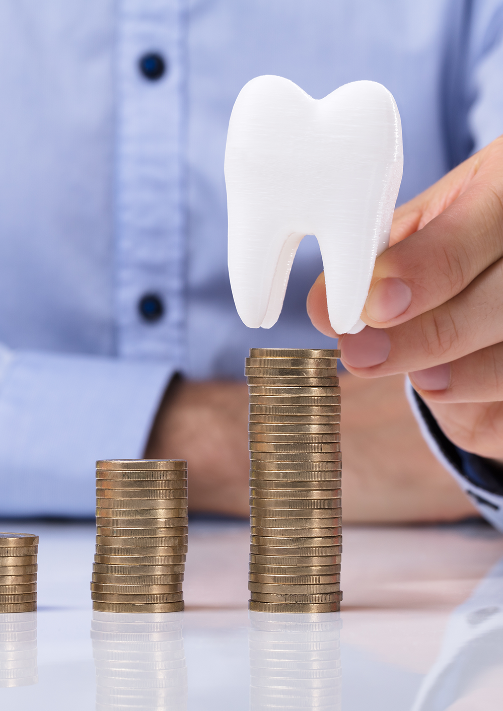 Dental accountant placing model tooth on stack of coins