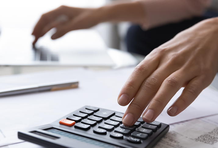 Close-up of accountant using calculator and scanning tax documents