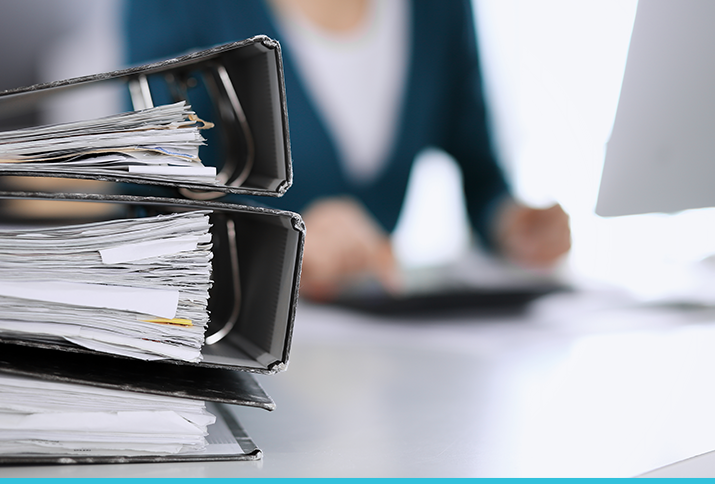 A stack of tax binders in front of a busy accountant