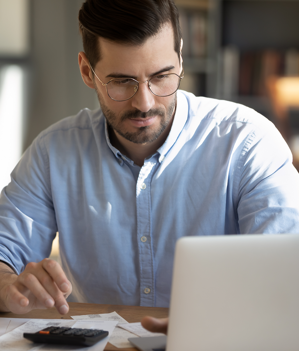 Serious man in glasses planning taxes on laptop