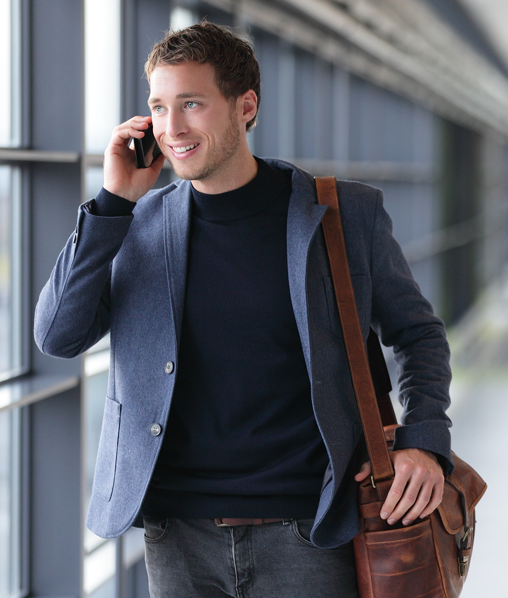 Smiling young businessman talking on mobile phone