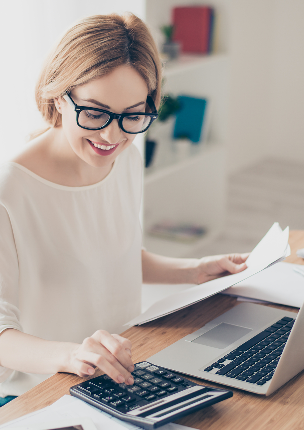 Woman in glasses using calculator for taxes