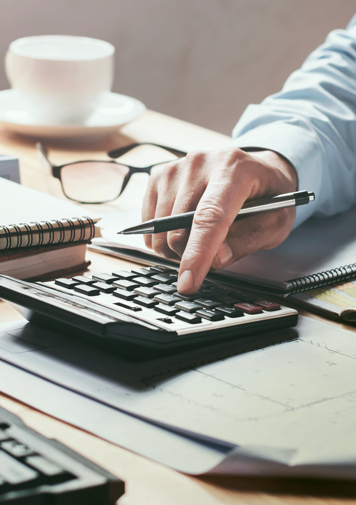 Accountant using calculator on cluttered desk