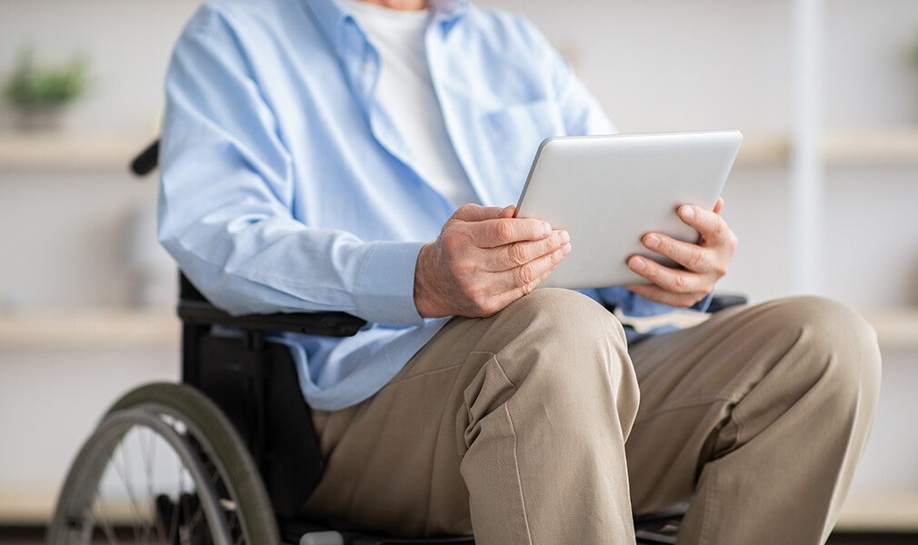 Elderly man in wheelchair reviewing disability insurance claim on tablet